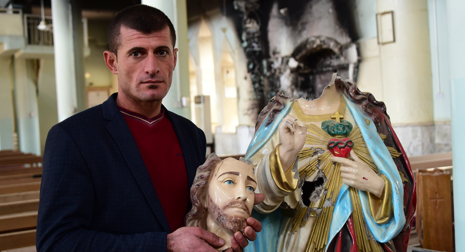 Iraqi Christian showing a decapitated statue of the Sacred Heart by Daesh (ISIS) in the Mar Addai Church, Karemlash, northern Iraq © Aid to the Church in Need
