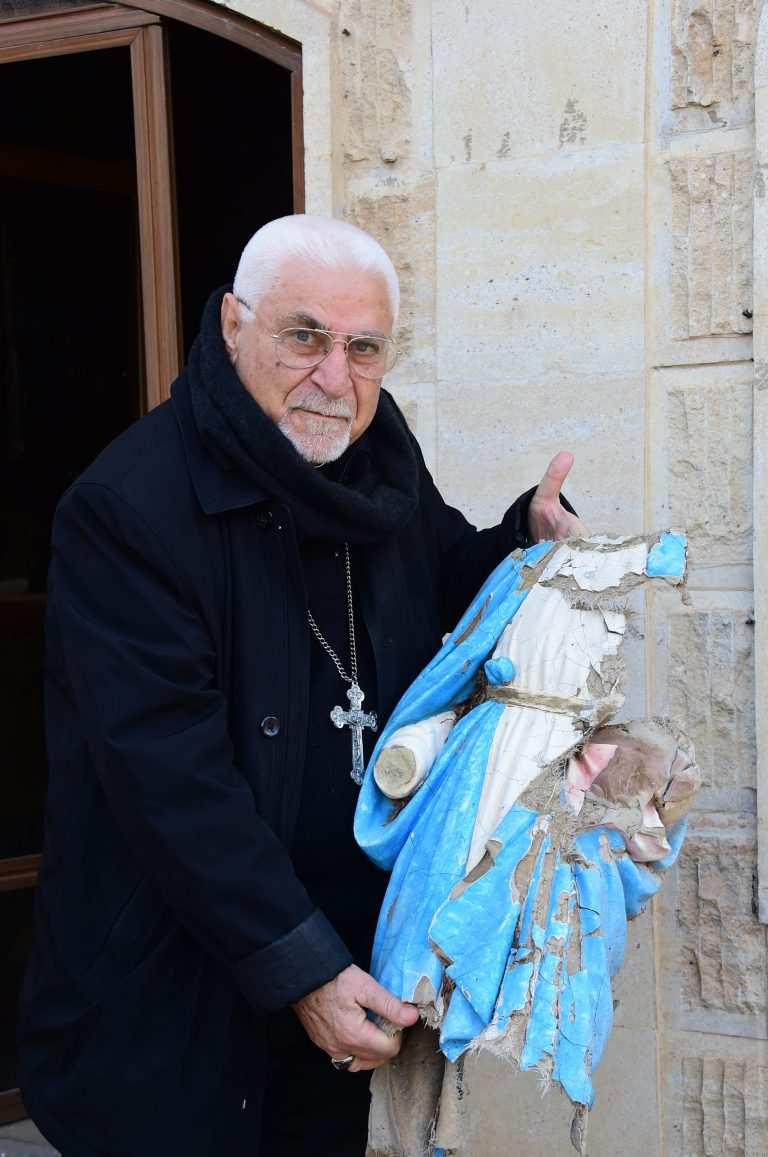 Archbishop Petros Mouche of Mosul at Saint George Syriac-Catholic Church holding a statue of Our Lady damaged by Daesh (© Aid to the Church in Need)