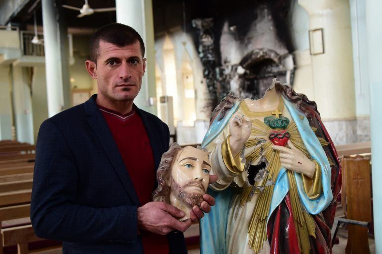 Christian holding the beheaded statue of the Sacred Heart - by Daesh (ISIS) - in St Addai Church, Iraq