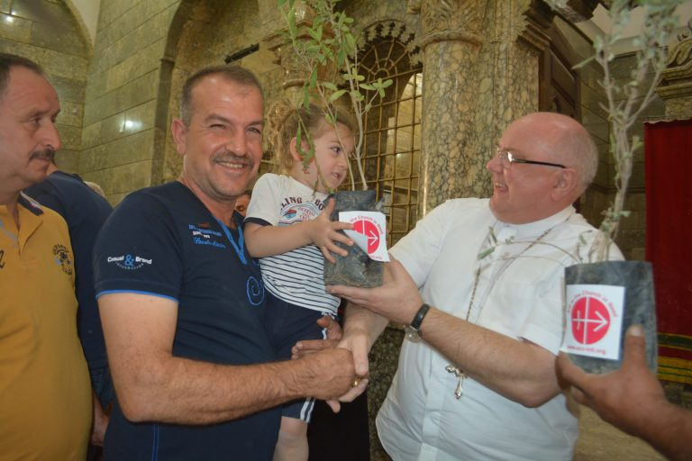 Aid to the Church in Need Middle East projects' coordinator Father Andrzej Halemba distributes olive tree to a Christian family at St George's Church, Bartela (© Aid to the Church in Need)