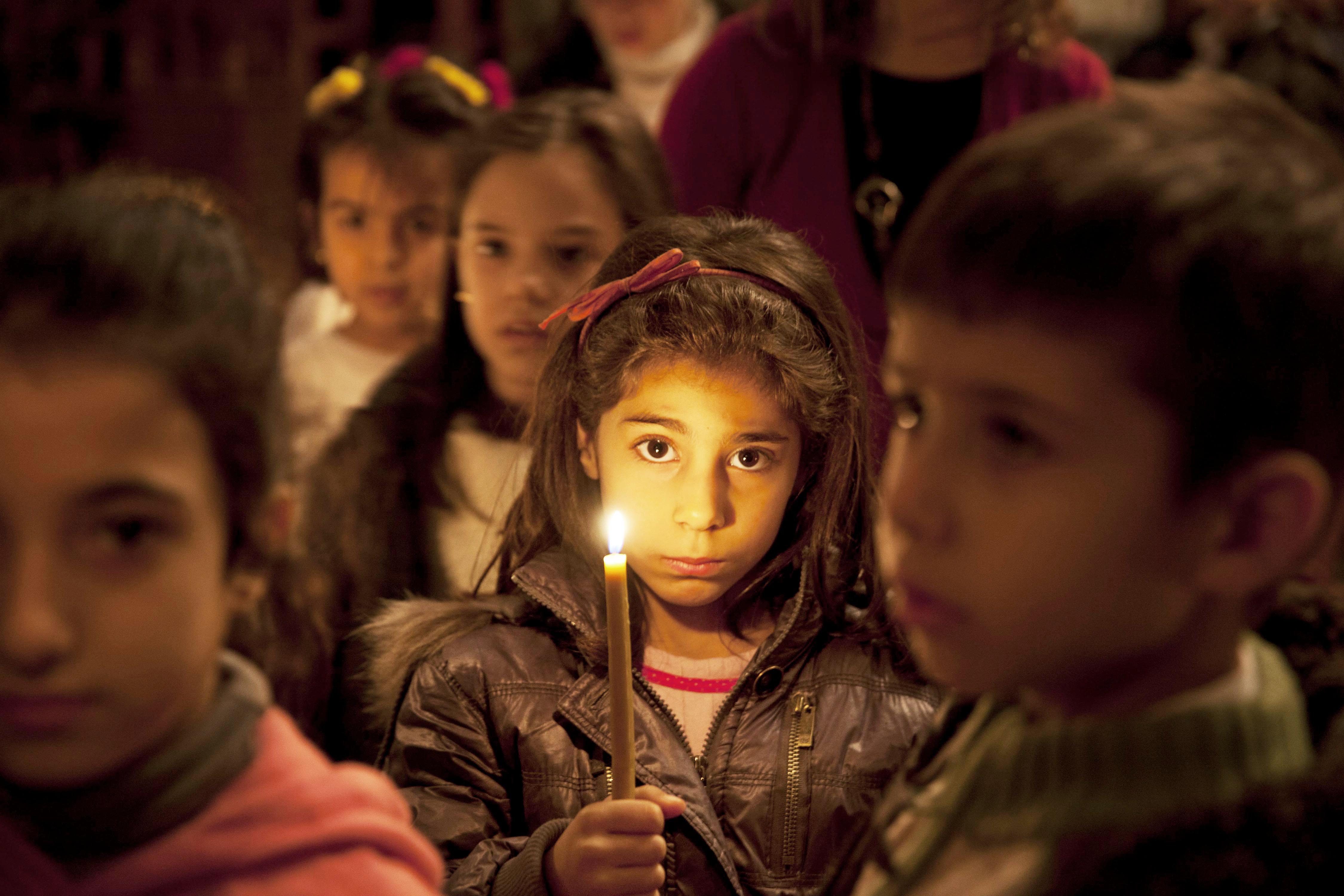 Young girl with a candle at Al-Zaytoun Melkite Greek Catholic Church, Damascus, Syria. (© Aid to the Church in Need)