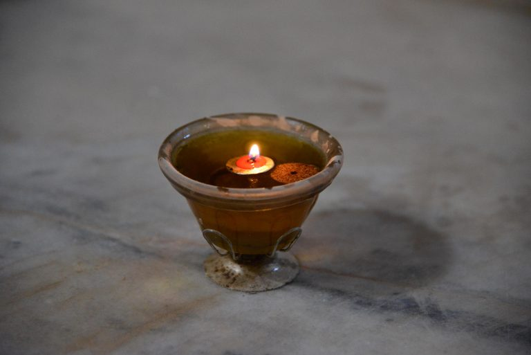 A candle lit on the round altar in the monastery of Mar Sarkis Maalula, Syria