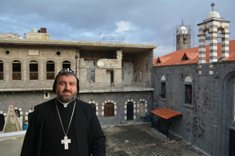Syriac Orthodox Archbishop Selwanos Petros Al-Nemeh of Homs and Hama, with Saint Mary Church of the Holy Belt in the background (© Aid to the Church in Need)
