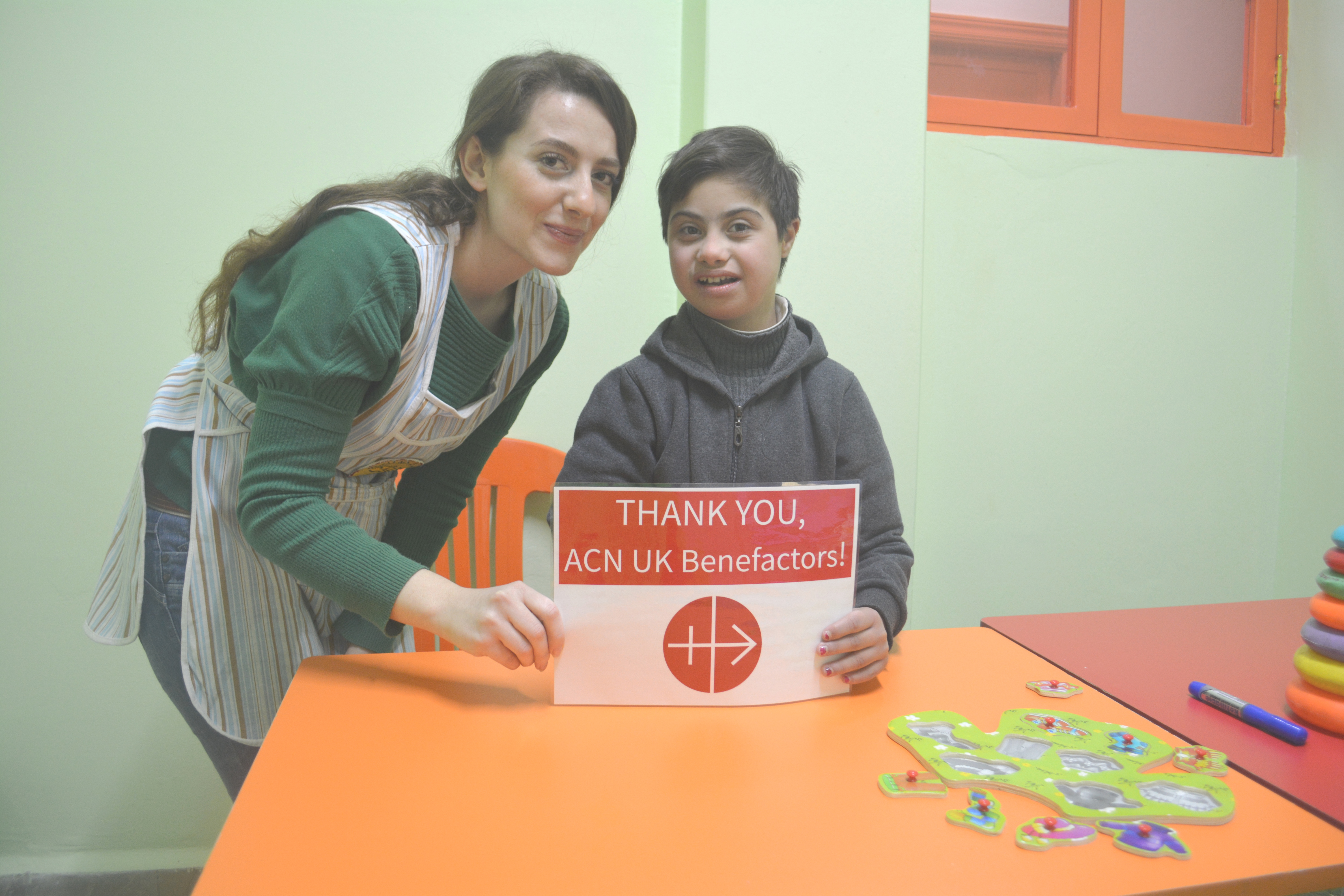 Supported by her teacher, a youngster at the Mustard Seed centre in Homs shows her appreciation