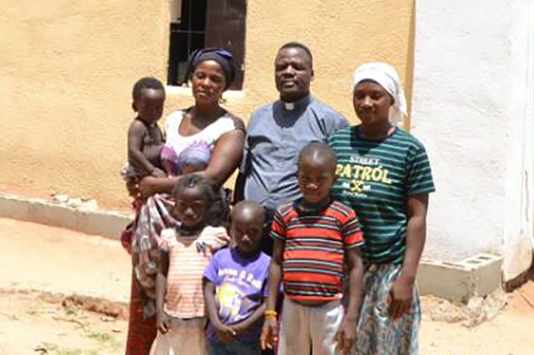 Bereaved families with priest in Asso village, Kaduna state, Nigeria: Mrs Blessing Stephen (left) with children Goodwin, Emmanuelle, Miracle, Father Alexander Yeyock, Mrs Evelyn Martins and son, Humble (© ACN-Fr A Yeyock)