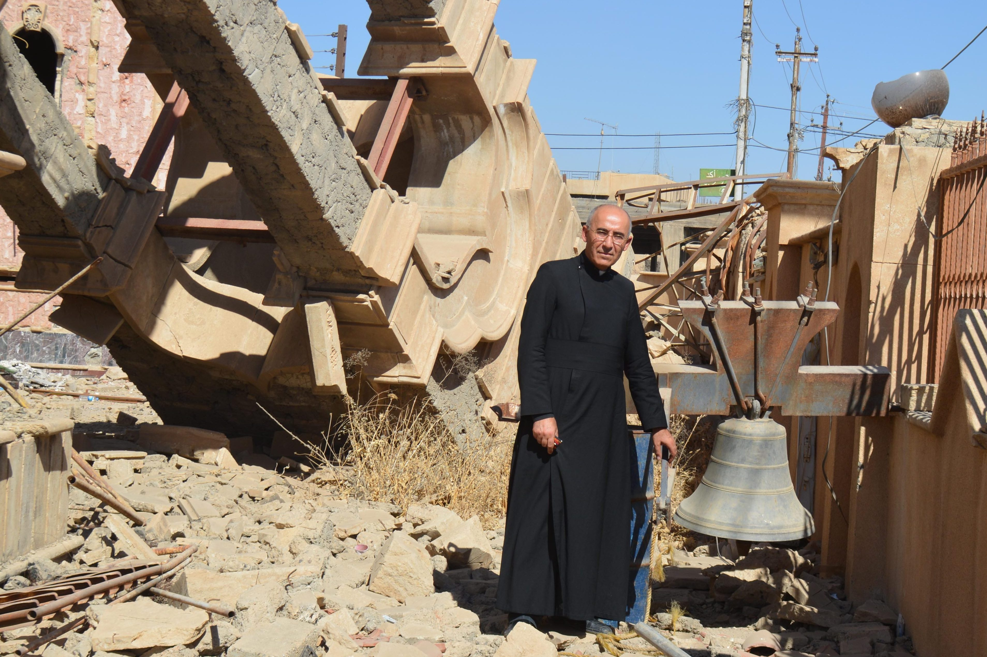 Father Georges Jahola in front of St Behnam Church's bell tower destroyed by Daesh (ISIS) (©Aid to the Church in Need)