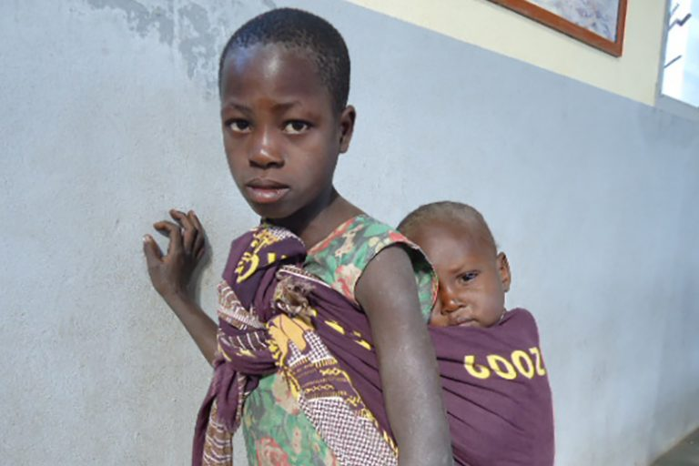 Young girl carrying a child in a cloth on her back in Tete Diocese, Mozambique (© ACN)