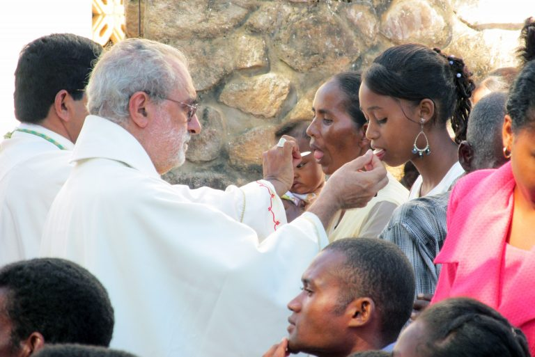 Bishop Vella distributes holy communion.