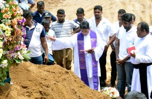 Common Funeral Service for Easter Sunday Victims at St. Sebastian's Church in Katuwapitiya, Negombo (Sri Lanka) on 23.04.2019: Malcolm Cardinal Ranjith, the Archbishop of Colombo, presided over a funeral service for a group of victims at 10.00am at the church premises. The coffins were brought to the premises one at a time for the services amidst intense security. Funeral services and the burials took place in an atmosphere of heavy grief and sorrow with relatives and friends weeping and mourning for the unexpected loss of their loved ones. Photo: Priest blessing the graves of the victims