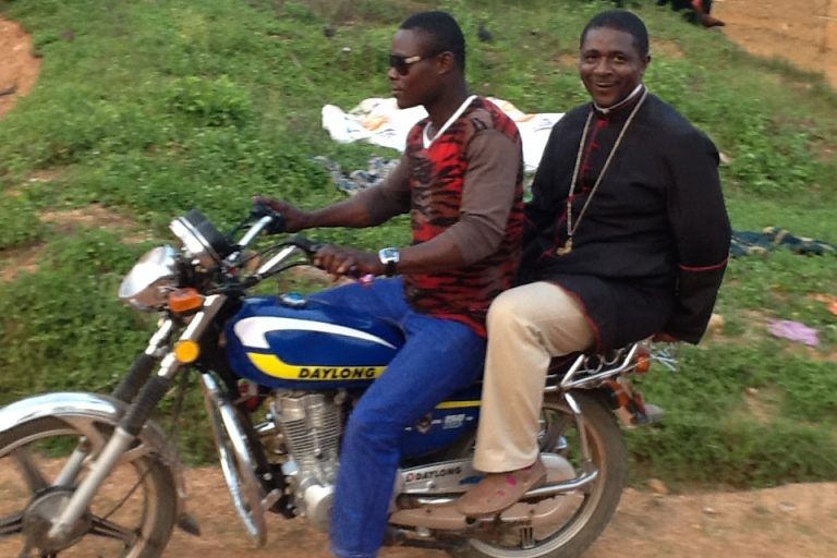 Bishop Andrew Nkea (right) on a motorcycle (©: ACN)