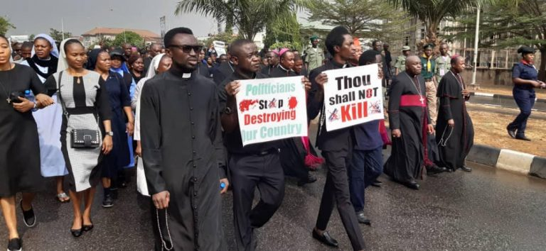 "Catholic bishops in Nigeria lead a peaceful protest; Father Sebastain Sanni holds a placard saying ""Thou shall not kill"" during the march (Credit: Aid to the Church in Need)"
