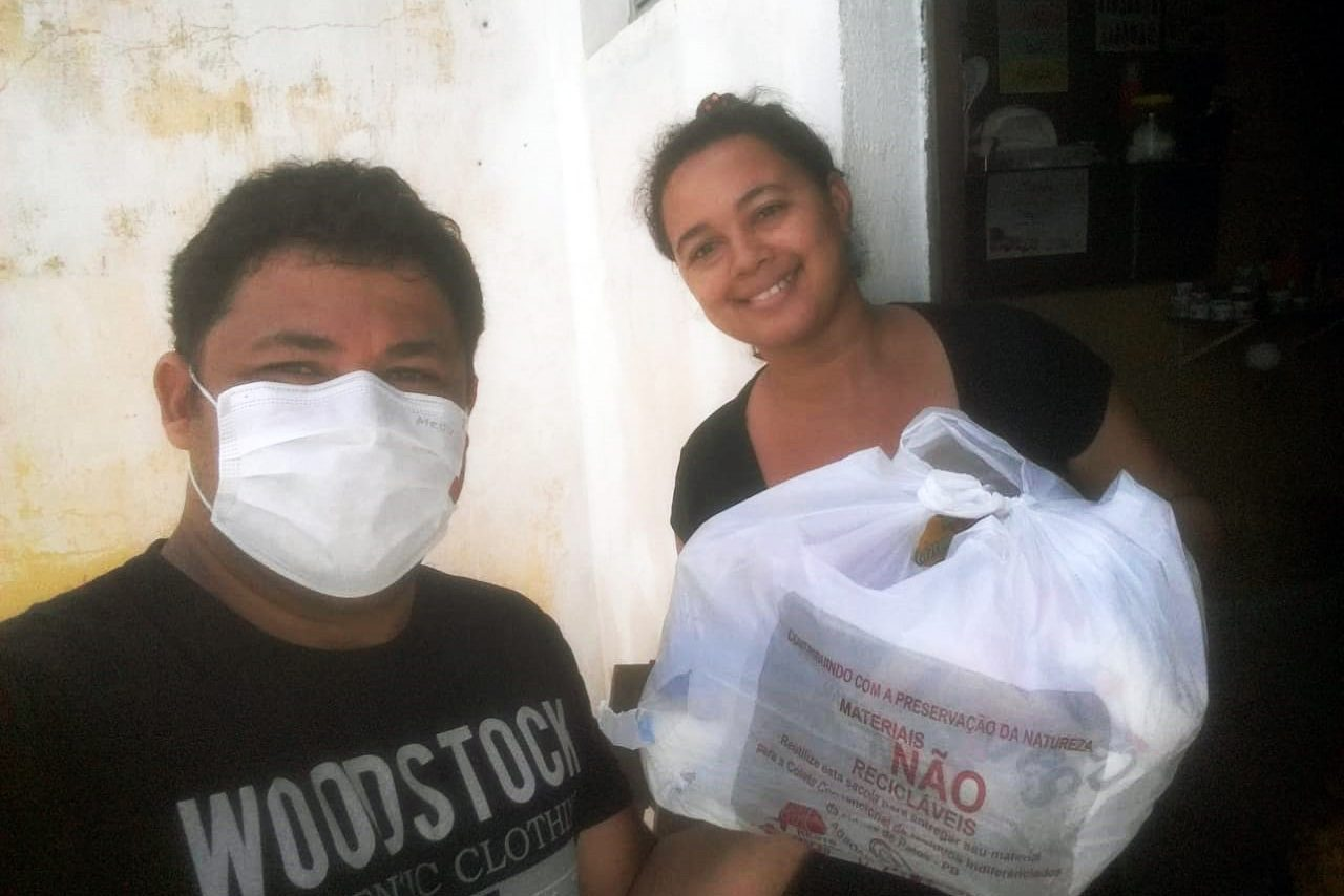 A lay member of Brazil's Shalom Community delivers a food parcel during the pandemic