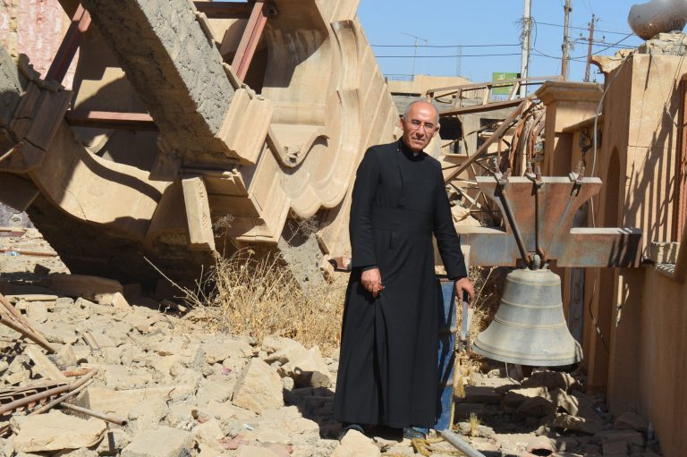 Syriac Catholic priest Father George Jahola next to the remains of the belltower of the Syriac Catholic Mar Benham Church in Baghdeda (Qaraqosh)