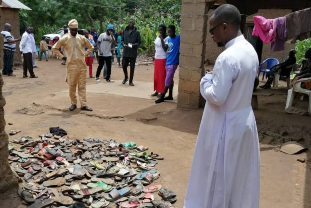 Fr. Sam Ebute in front of the dead's footwear (©Aid to the Church in Need)