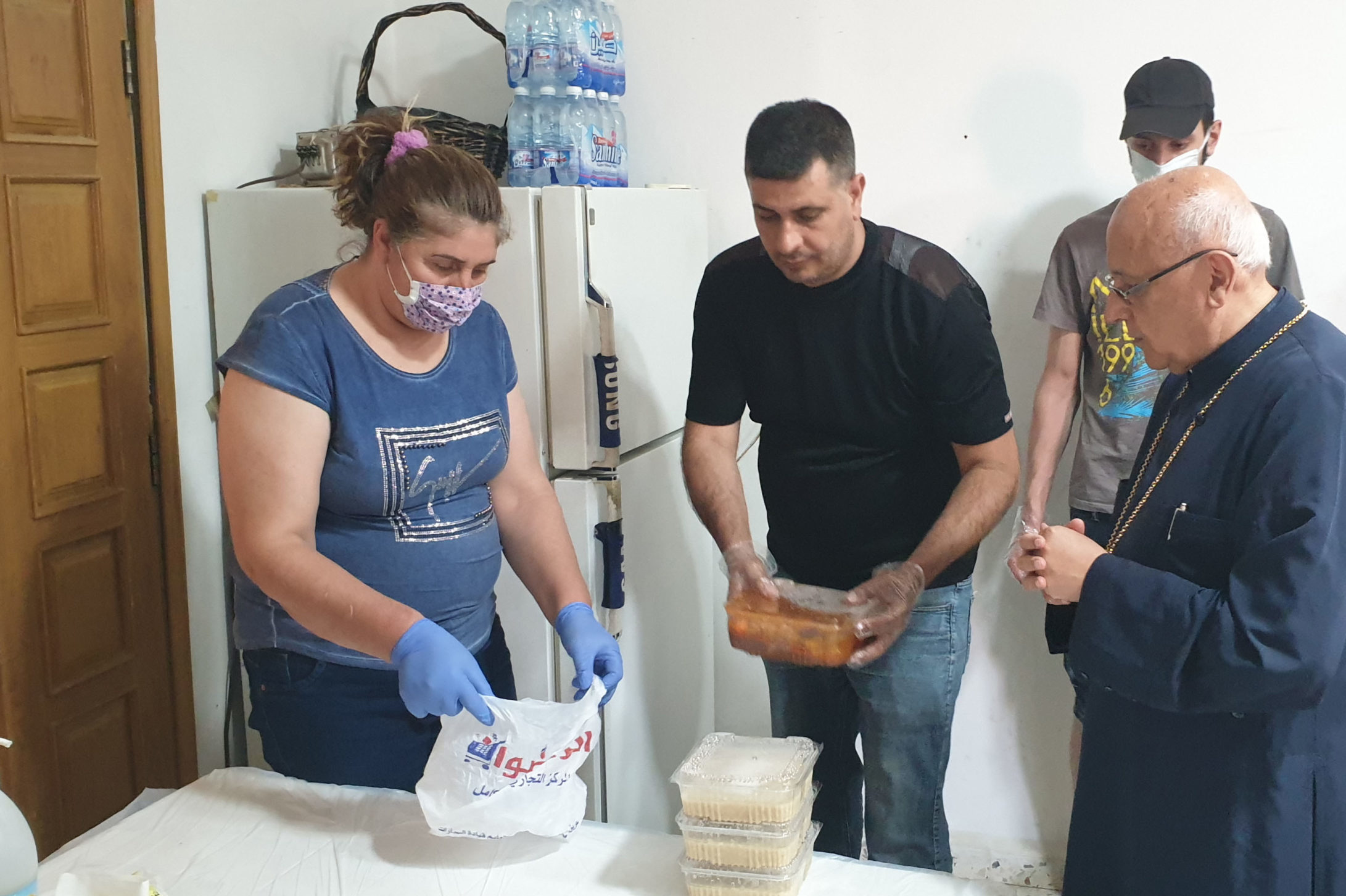 Preparing to distribute food to Syrian refugees, observing Lebanese COVID-19 safety guidance.