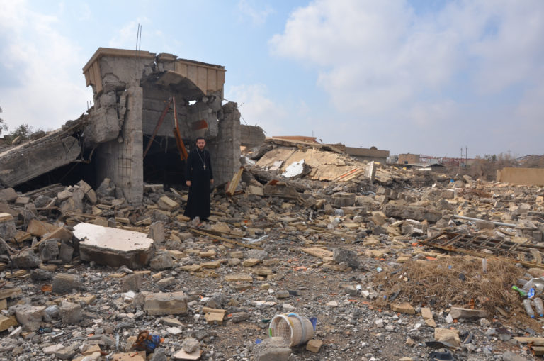 With image of a priest standing amid the ruins of a building in Bashiqa destroyed during Daesh (ISIS)'s occupation of the town (Image © Aid to the Church in Need)